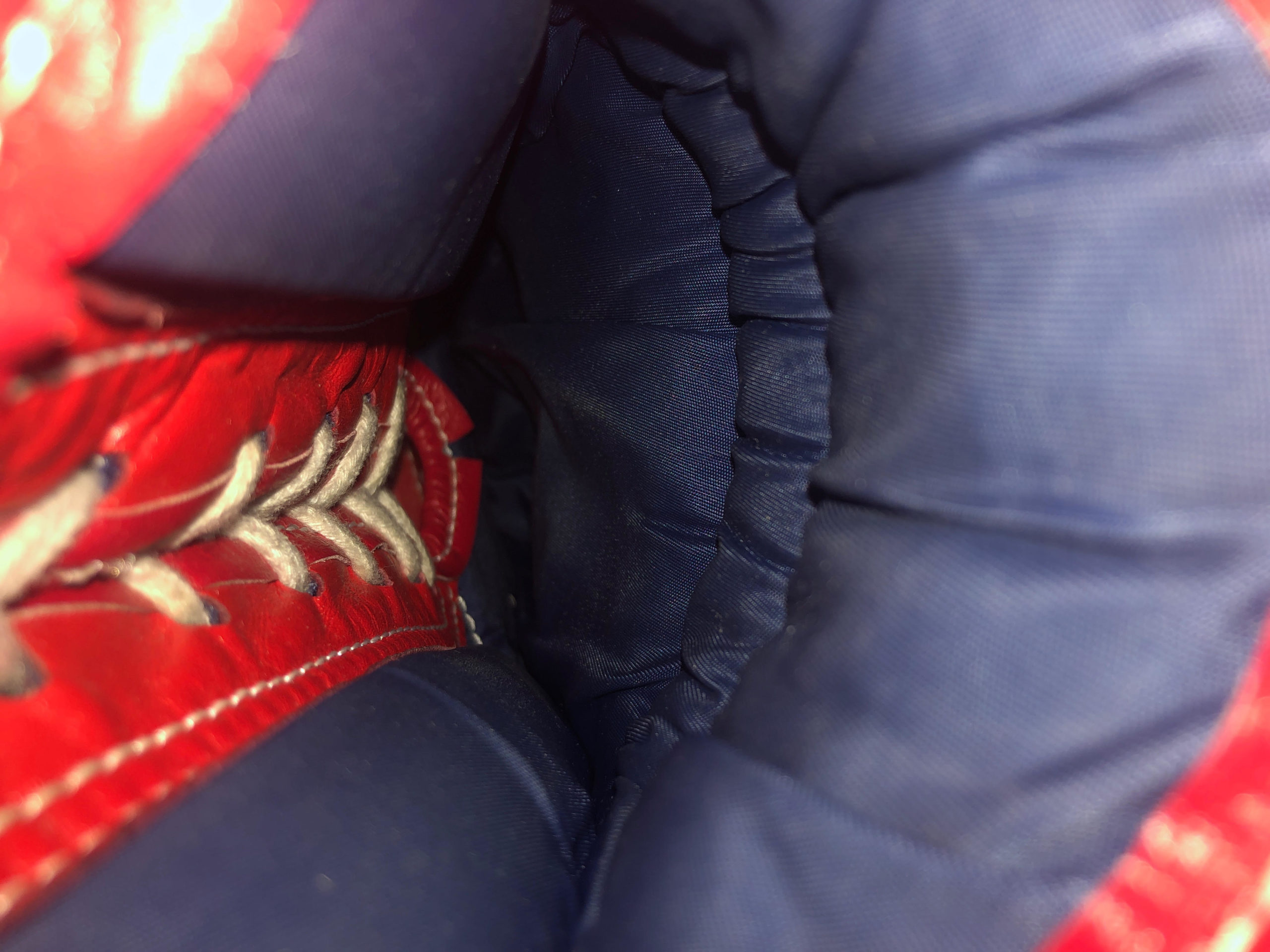 Extreme close up photo of the inside of a boxing glove with red and blue fabric and laces.