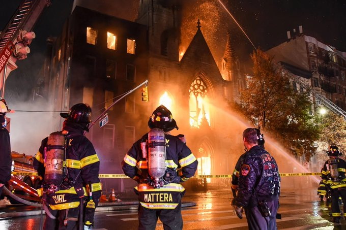 A photo of a church on fire with flames coming out of the front steeple and windows. There are three firemen in the foreground with their backs to the camera. A couple of fire hoses point their spray at the building