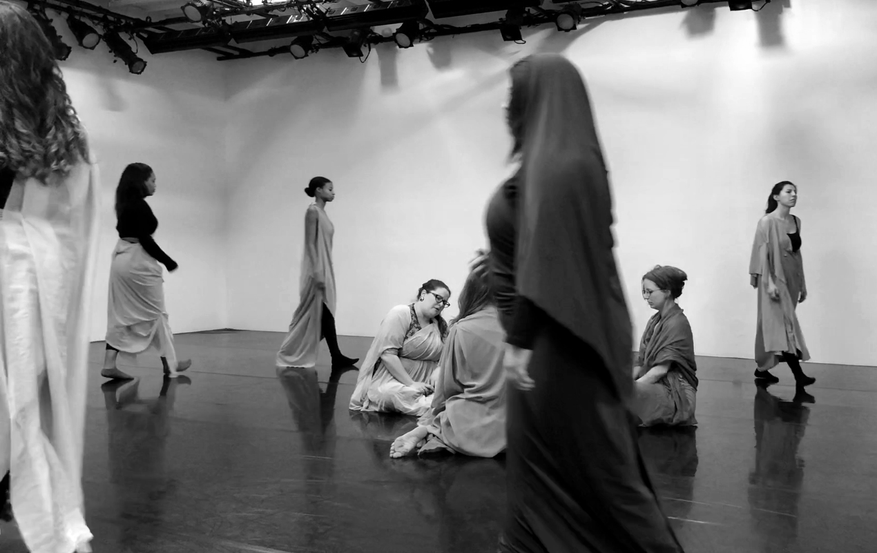 A black and white photo of a white walled performance space. There are 8 women in shawls, both women of color and white. Some are sitting in a circle in the middle of the room, and there are a number of women walking in a circle around the perimeter of the room.