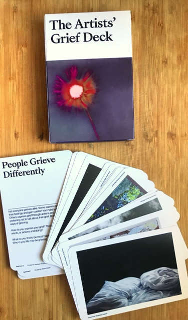 "A photo of a table top with a box and cards splayed. The box says ""The Artists' Grief Deck"" and there is a purple watercolor painting with a red/pink starburst. The splayed cards are like playing cards. One is visible and it reads ""People Grieve Differently"". The other cards have photos and images. One is a painting or photo of white bedsheets on a black background."