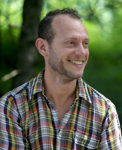 A color headshot of a white male presenting person with short hair. He is wearing a flannel shirt. There is greenery in the background.