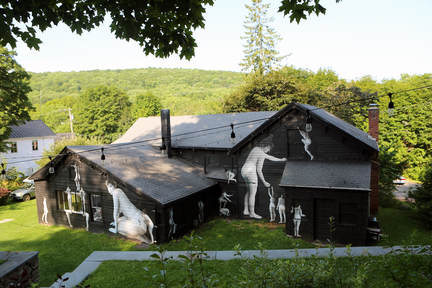 A photograph of a wood panelled house, painted black and nestled amongst a valley of green trees. Black and white xeroxed photos are pasted on the house, some as large as the house, others human-sized. They depict a woman in their underwear in various poses.