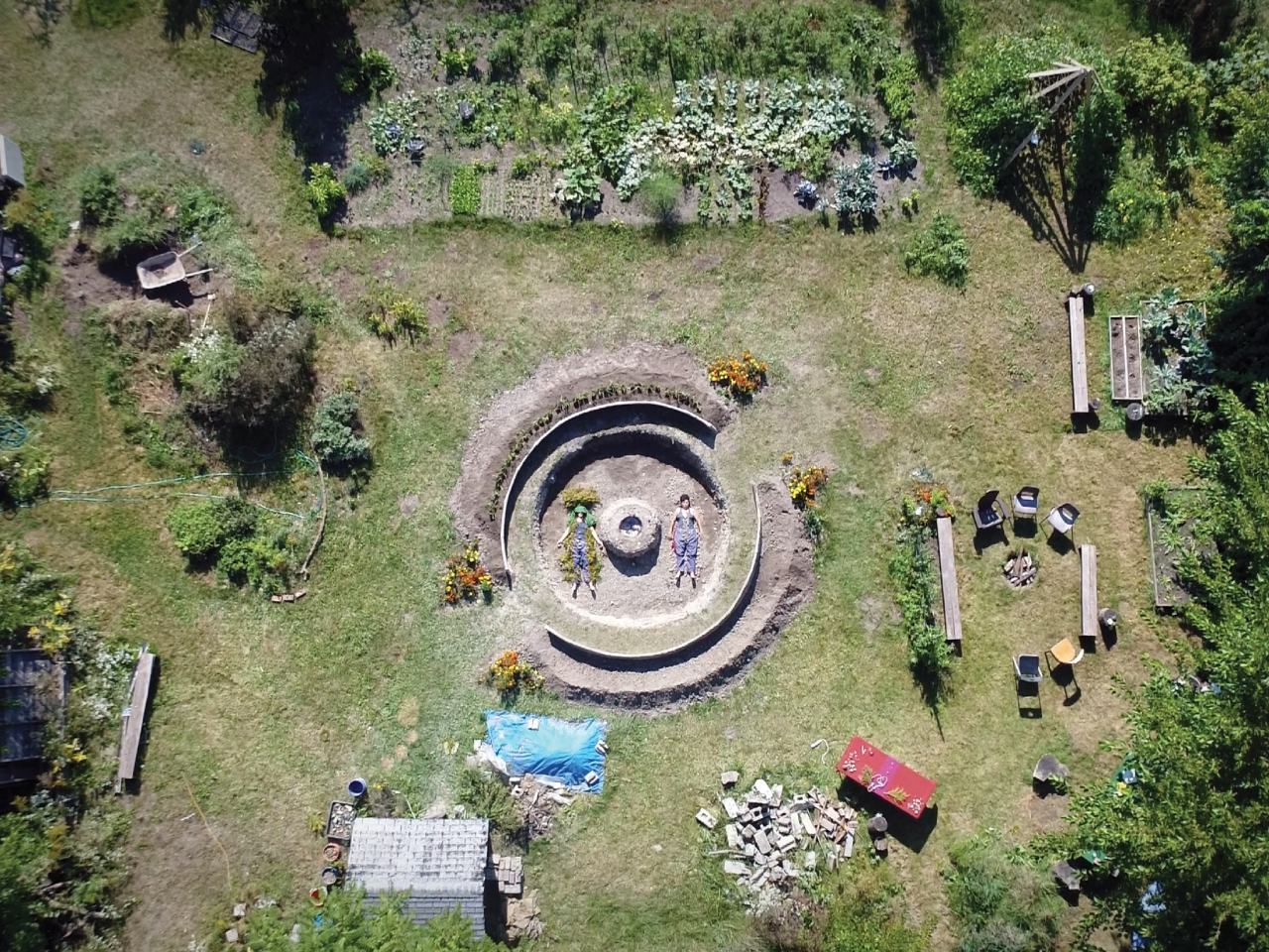 A drone photograph looking directly down on a scene of a garden/park. There is a central circle that has been dug out of the earth. There are two bodies laying in the raw earth circle. Around the circle there are vegetable garden beds, a shed roof, bricks strewn in a pile, a blue tarp covering a mound, and a circle of chairs and benches.