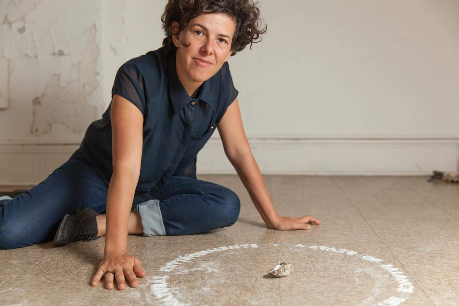 A photo of a person with short tousled brown hair wearing jeans and a dark blue shirt. they are crouched on the floor in front of a circle made with a white powder.