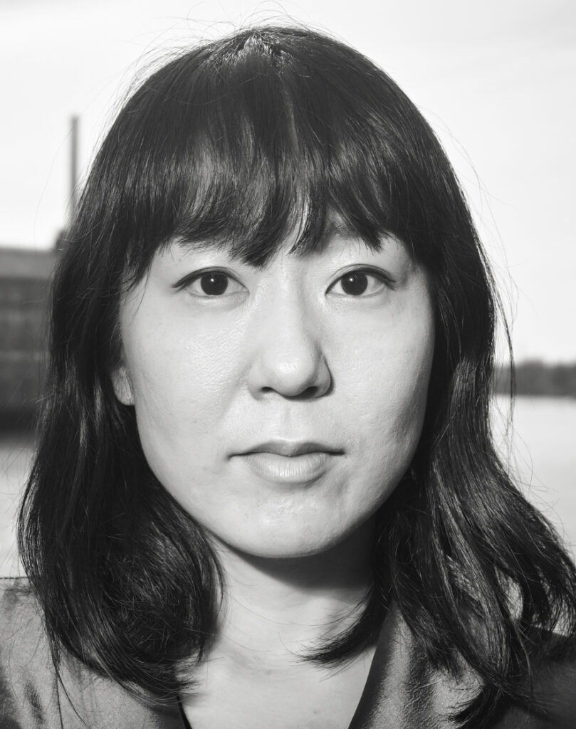 A black and white headshot of an Asian female presenting person with shoulder length dark hair and bangs.