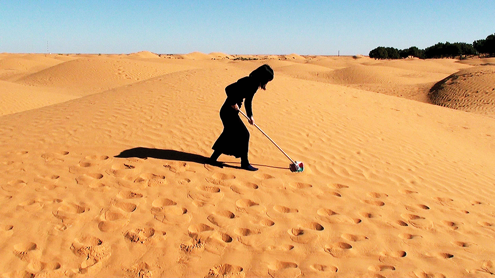 A photograph of the yellow sand dunes of the desert. There are some trees in the far distance on the right of the frame. In the middle of the photo is a woman dressed in black, with black shoulder-length hair and black socks. The only skin you see is their hands. They have a broom in their hands and they are making a sweeping action on the sand.
