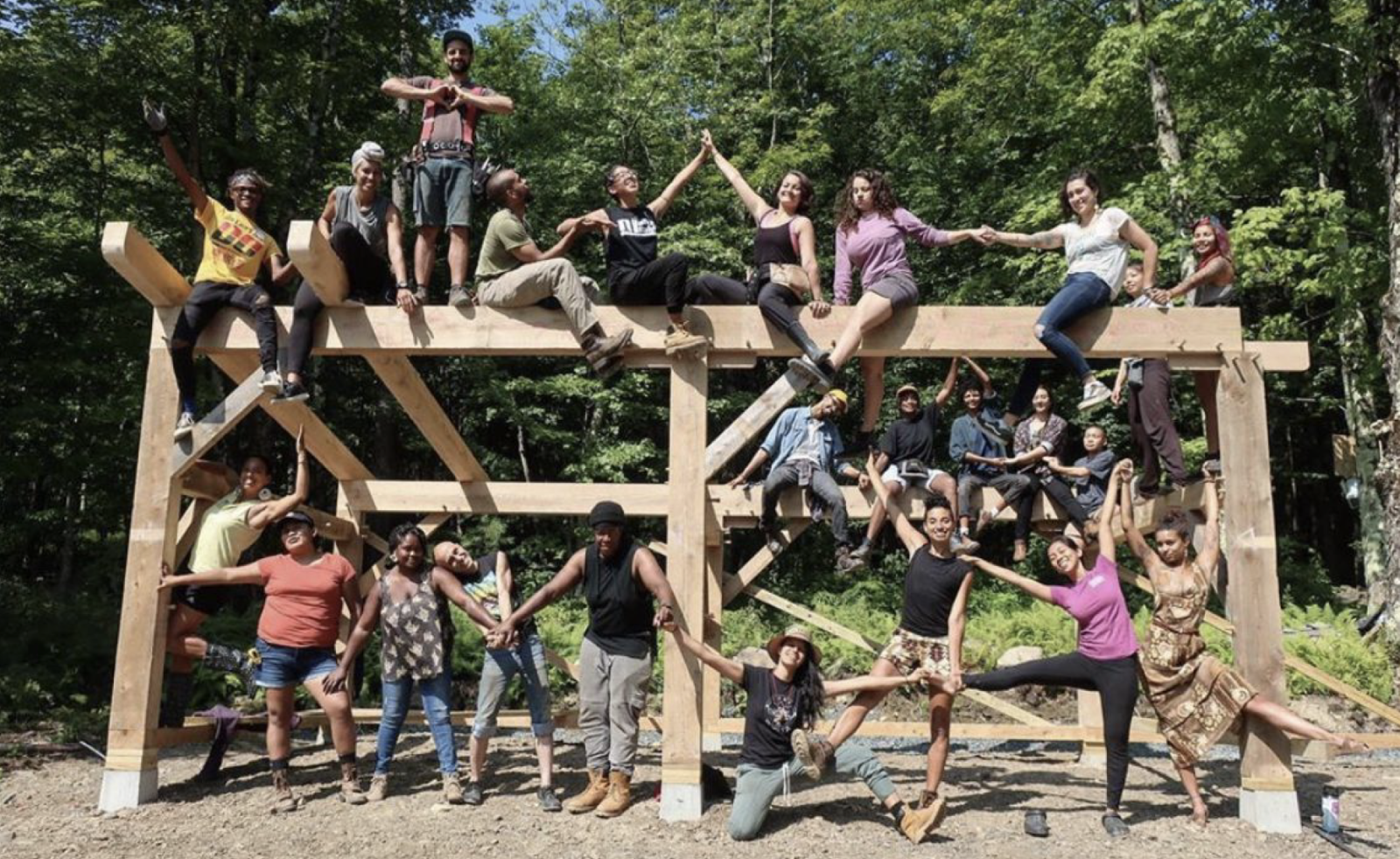 A photo of a group of young BIPOC people posing under, amongst, and on top of a timber structure.