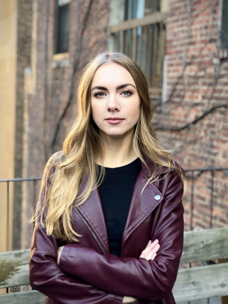 A portrait color photo of a female presenting white person with long blond hair. She is wearing a maroon leather jacket.