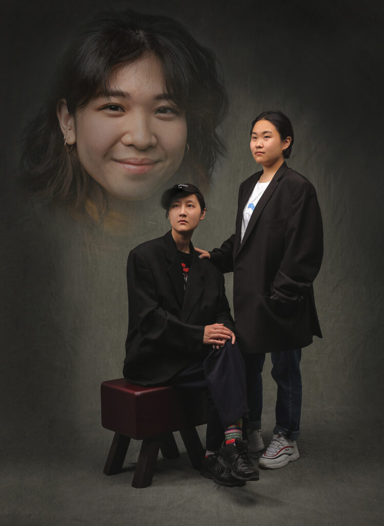 A photo of three people, staged like a traditional studio portrait with a grey photo backdrop. There are two people in the photo, a female presenting Asian person standing and a male presenting Asian person sitting on a stool, both wearing black. They are looking off frame into the distance. The third person is super imposed into the upper left quadrant of the photo with a vignette around their face. They are a female presenting Asian person with brown hair.