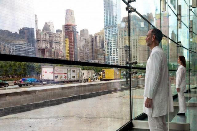 Photo documentation from Ernesto Pujol's project, 9-5 in 2015. Two performers in white clothing look out to a city landscape from inside a glass walled building.