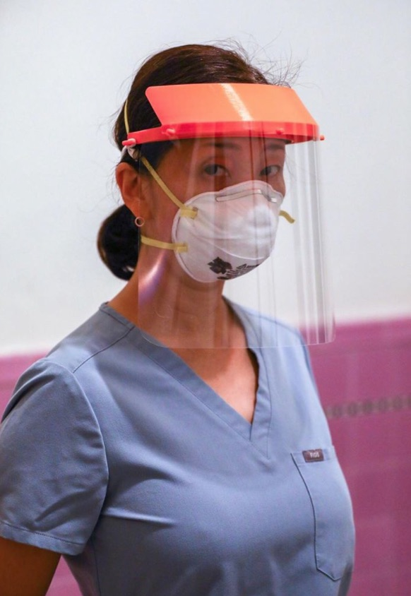 A woman in blue scrubs wears a protective face shield and face mask